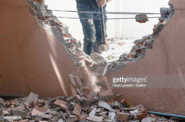 midsection of construction worker demolishing wall with sledgehammer - demolishing stock pictures, royalty-free photos & images