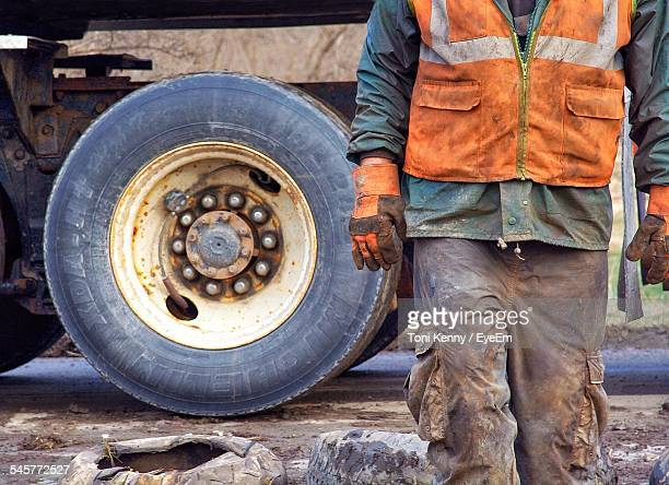 Midsection Of Construction Worker Walking Against Truck