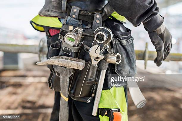Midsection of construction worker wearing tool belt at site