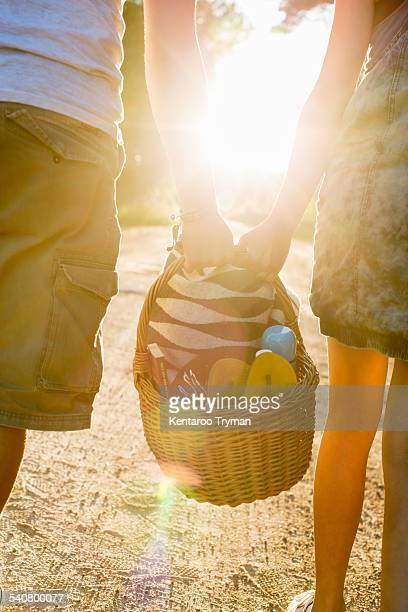 Midsection of couple carrying picnic basket against bright sun