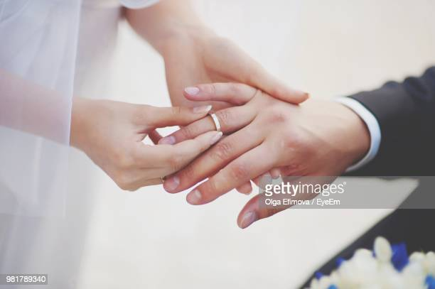 midsection of couple exchanging wedding ring - matrimonio foto e immagini stock