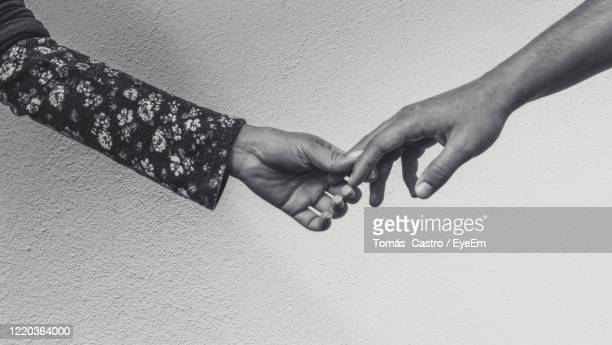 midsection of couple holding hands against wall - altruismo foto e immagini stock