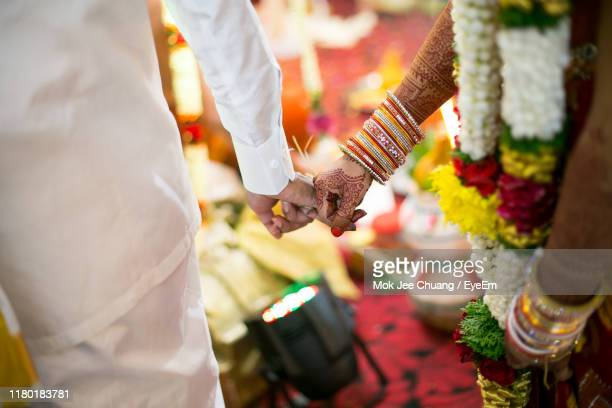 midsection of couple holding hands during wedding ceremony - newlywed stock pictures, royalty-free photos & images