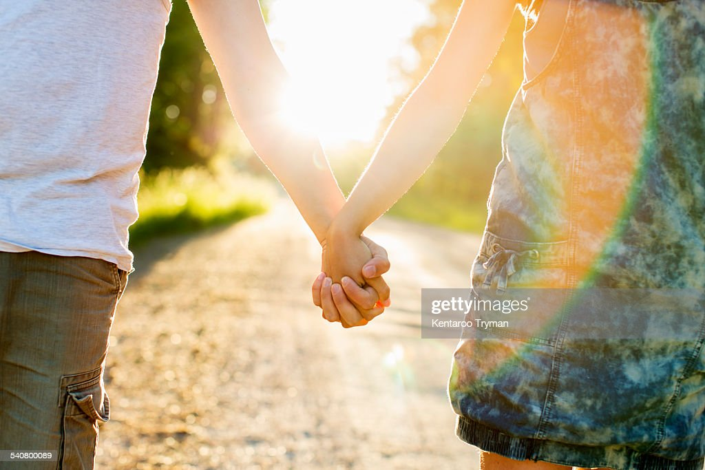 Midsection of couple holding hands on dirt road against bright sun : Stock Photo