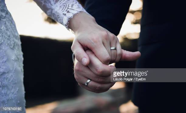 midsection of couple holding hands - married stock pictures, royalty-free photos & images