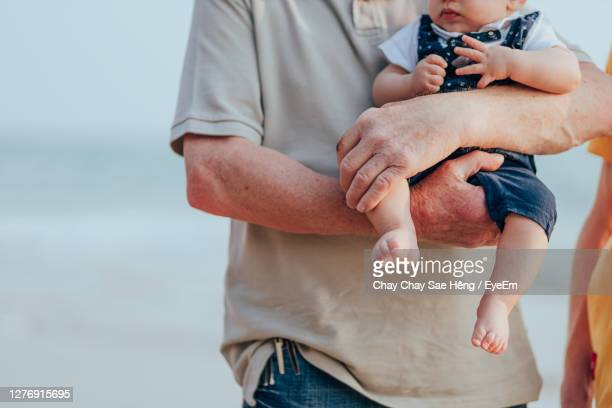 midsection of couple holding hands - catching stock pictures, royalty-free photos & images