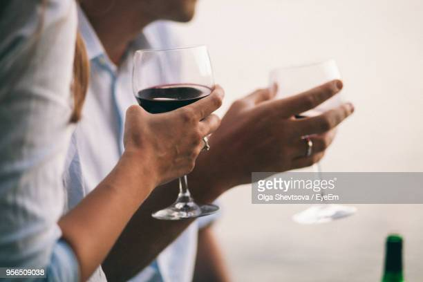 Midsection Of Couple Holding Wineglasses