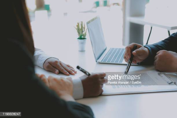midsection of couple signing contract paper by lawyer at desk - signing stock pictures, royalty-free photos & images