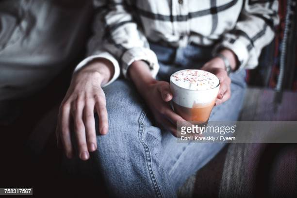 Midsection Of Couple Sitting With Coffee Drink