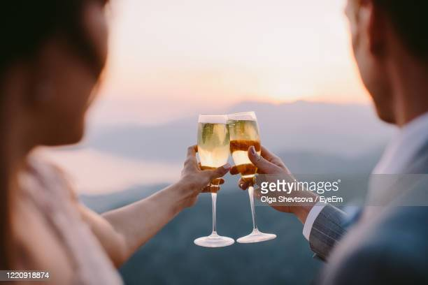 midsection of couple toasting drink - celebratory toast stock pictures, royalty-free photos & images
