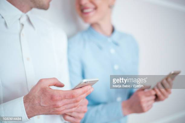 midsection of couple using mobile phone against wall - marija mauer stock-fotos und bilder