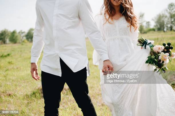 midsection of couple with holding hands walking on field - wedding stock pictures, royalty-free photos & images