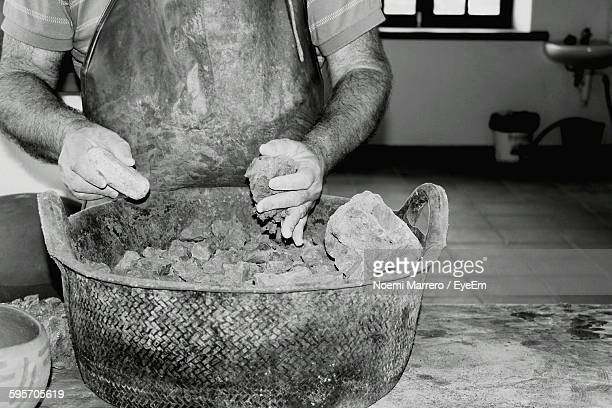 Midsection Of Craftsperson Holding Clay At Workshop