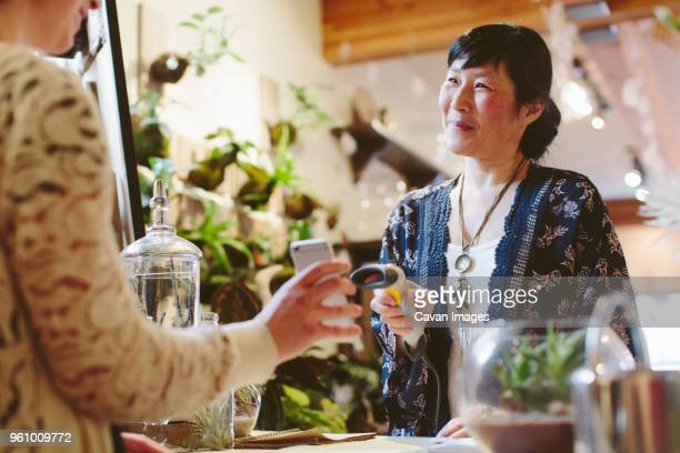 midsection of customer holding mobile phone while smiling owner scanning qr code in plant shop - cavan images foto e immagini stock