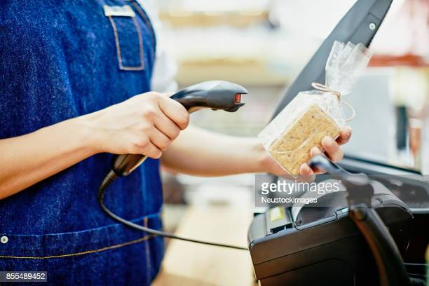 midsection of deli owner scanning barcode on food package - convenience store counter stock photos and pictures