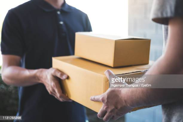 midsection of delivery person giving boxes to young man at home - recibir fotografías e imágenes de stock