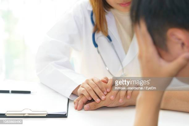 Midsection Of Doctor Consoling Patient At Desk In Office