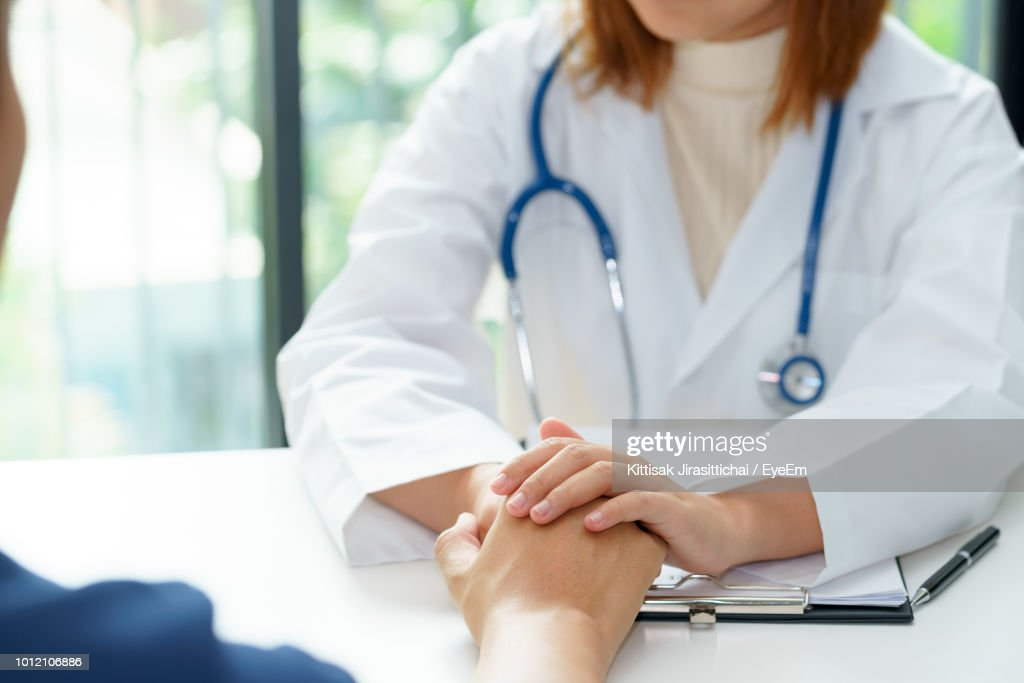 Midsection Of Doctor Consoling Patient : Stock Photo