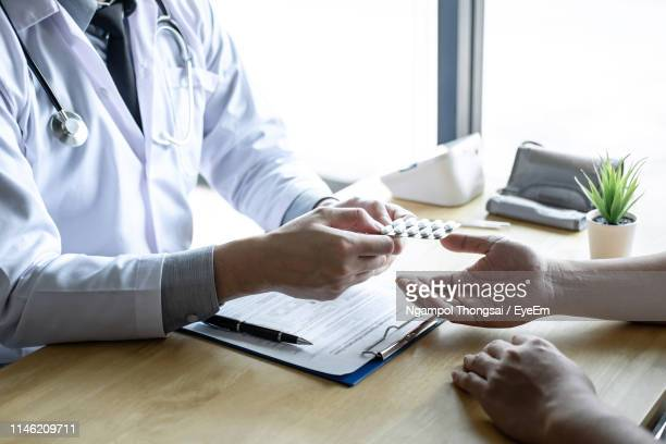 midsection of doctor giving medicine to patient at clinic - blister pack stock pictures, royalty-free photos & images