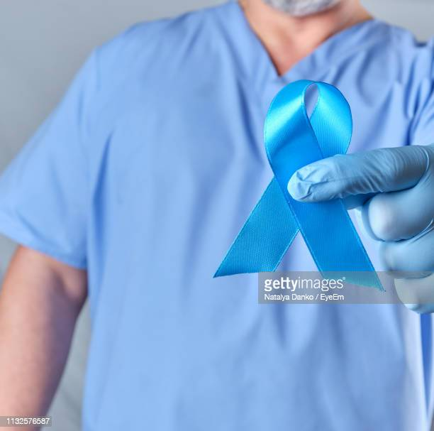 midsection of doctor holding blue breast cancer awareness ribbon - blue cancer ribbon stock photos and pictures