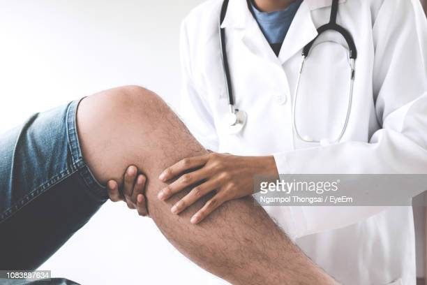 midsection of doctor holding patient leg in clinic - knee stock pictures, royalty-free photos & images