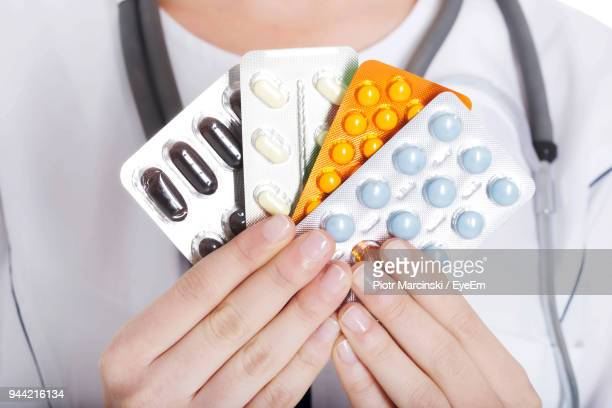 Midsection Of Doctor Holding Pills