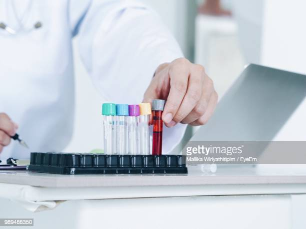Midsection Of Doctor Holding Test Tube On Desk At Hospital