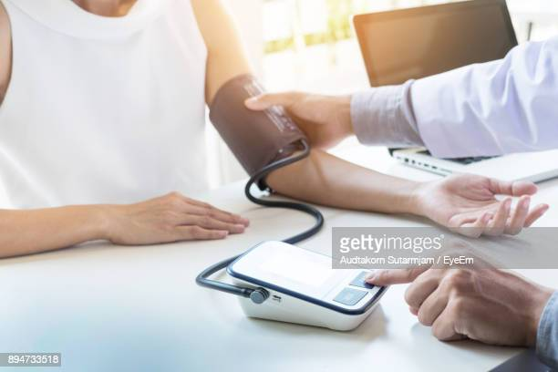Midsection Of Doctor Measuring Patient Blood Pressure At Table