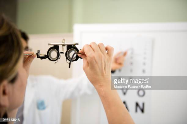 midsection of doctor showing alphabets to patient during eye test - eye chart stock pictures, royalty-free photos & images