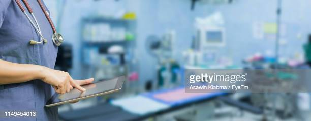 midsection of doctor using digital tablet in operating room - medical building stock pictures, royalty-free photos & images