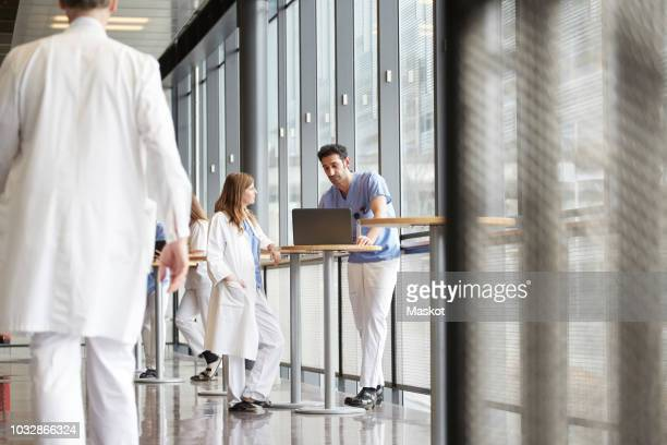 Midsection of doctor walking while healthcare workers discussing over laptop in corridor at hospital