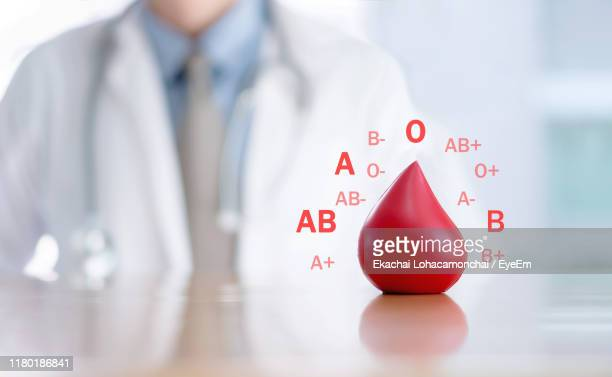midsection of doctor with blood sign on desk in hospital - blood group stock pictures, royalty-free photos & images