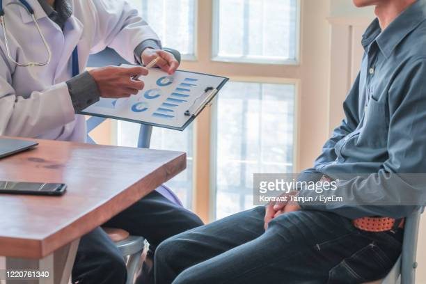 midsection of doctor with patient in clinic - erectile dysfunction stock pictures, royalty-free photos & images
