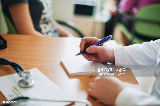 Midsection Of Doctor Writing On Book At Table