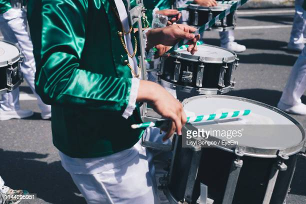 midsection of drummers playing drum while walking on road - parade stock pictures, royalty-free photos & images