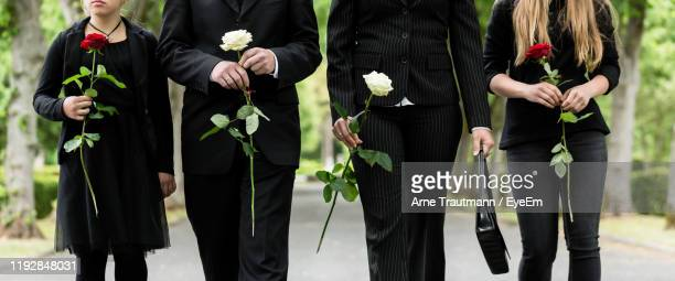 midsection of family holding roses on road during funeral - funeral stock pictures, royalty-free photos & images