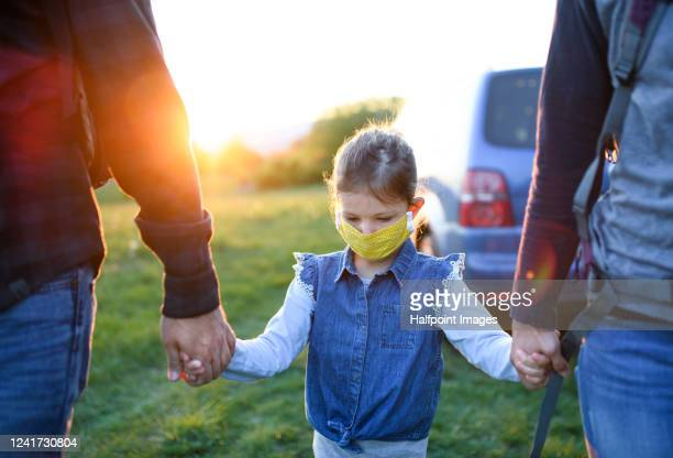 midsection of family with small girl with face mask outdoors in spring nature, walking. - mittlerer teil stock-fotos und bilder