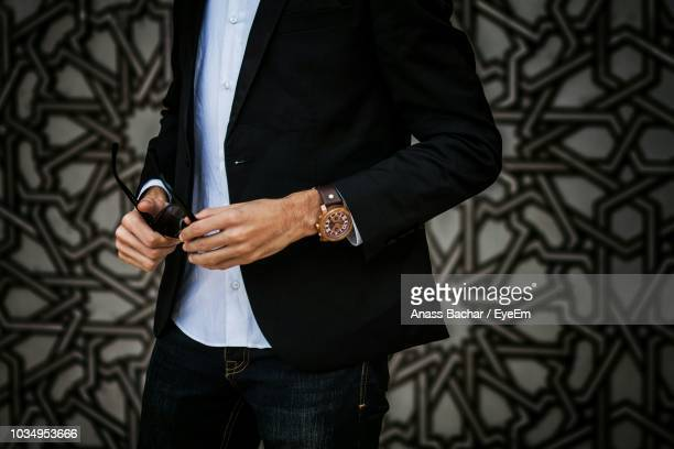 Midsection Of Fashionable Man Wearing Suit While Holding Sunglasses