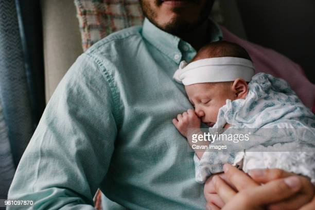 midsection of father carrying sleeping newborn daughter while sitting on chair at home - birthing chair stock pictures, royalty-free photos & images