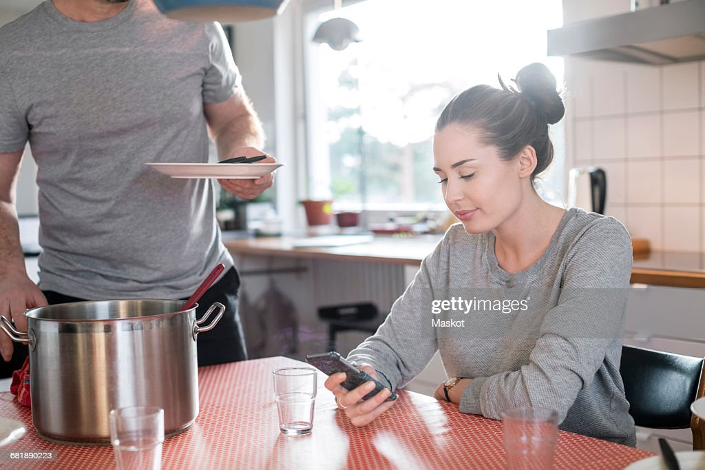 Midsection of father holding plate while daughter using smart phone at dining table in kitchen : Stock Photo