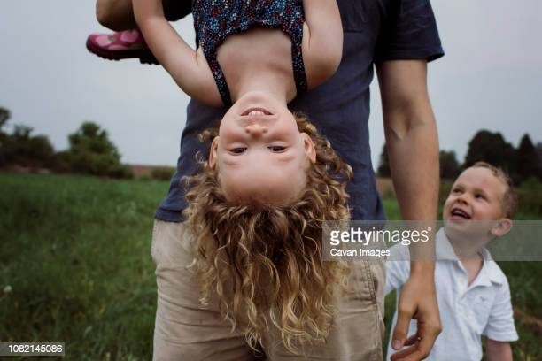 midsection of father picking daughter upside down while standing with son on grassy field against sky at park - op z'n kop stockfoto's en -beelden