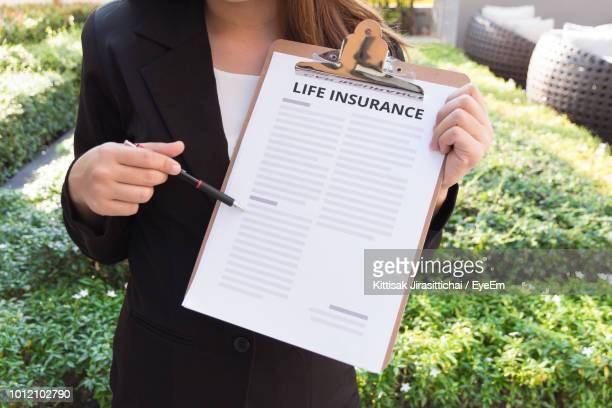 midsection of female agent with life insurance documents in yard - life insurance stock pictures, royalty-free photos & images