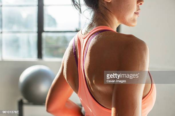 midsection of female athlete standing in gym - sports bra stock pictures, royalty-free photos & images