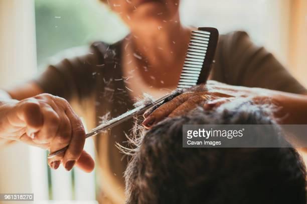 midsection of female barber cutting male customers hair - haare schneiden stock-fotos und bilder