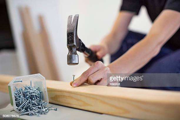 midsection of female carpenter hammering nail into wooden plank - hammer stock pictures, royalty-free photos & images
