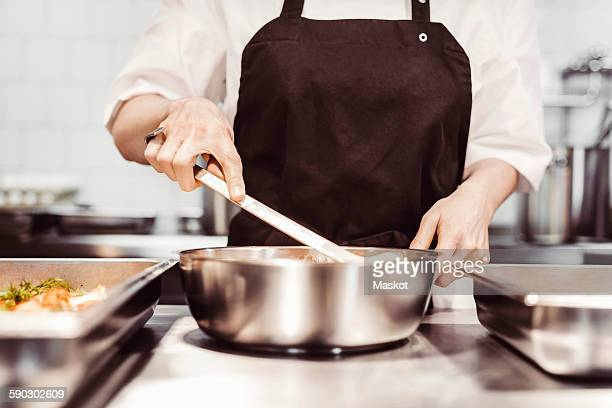 midsection of female chef preparing food at commercial kitchen counter - schort stockfoto's en -beelden
