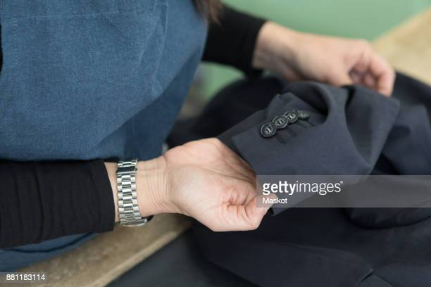 midsection of female cleaner checking suits sleeve at laundromat - 袖 ストックフォトと画像