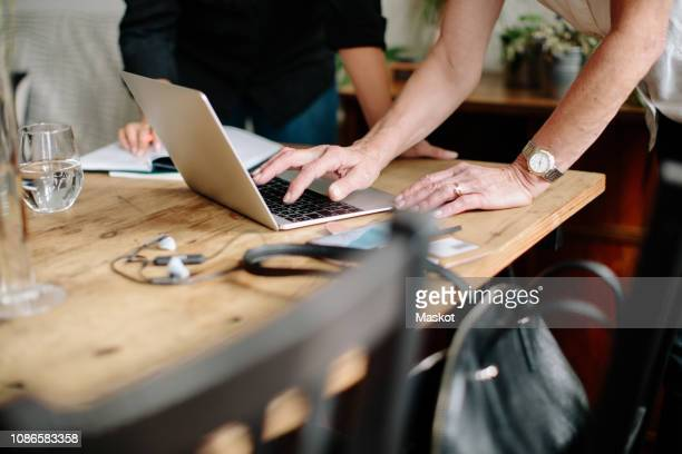 Midsection of female design professionals discussing over laptop at home office
