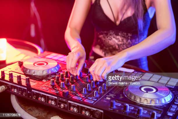 midsection of female dj playing music on turntable in nightclub - クラブdj ストックフォトと画像