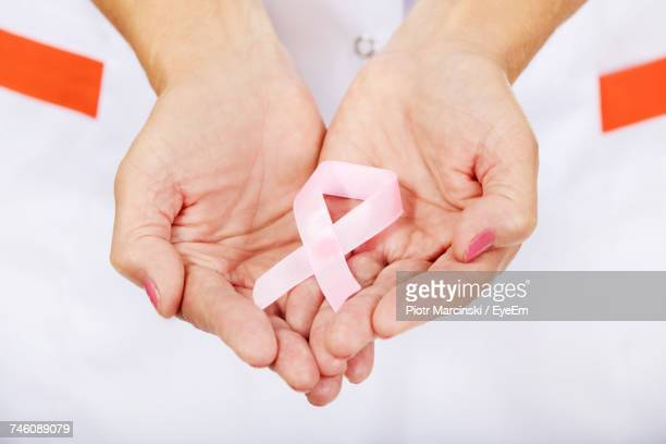 Midsection Of Female Doctor Holding Pink Breast Cancer Awareness Ribbon Against White Background